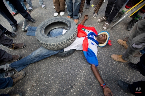 A man demonstrates what should be done with outgoing President Michel Martelly, during a protest demanding the Haitian leader's resignation, in Port-au-Prince, Thursday, Feb. 4, 2016. Haiti had been scheduled to hold a presidential runoff Jan. 24, but the election was canceled due to ongoing protests. Now Haitian officials are struggling to resolve their political and constitutional crisis before the scheduled end of Martelly's term that ends this weekend. Rumors have spread that Martelly will not leave office until a new president has been elected, spurring more protests. (AP Photo/Dieu Nalio Chery)