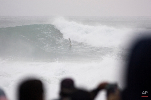 Ross Clarke-Jones, of Australia, rides out of a wave during the Eddie Aikau big-wave surfing contest in Waimea Bay near Haliewa, Hawaii on Thursday, Feb. 25, 2016. After days of massive waves in Hawaii, some reaching over 50 feet high and washing over roads and homes, organizers gave the nod Thursday morning to hold the rare big-wave surfing competition. Organizers of invitation-only Quiksilver In Memory of Eddie Aikau contest on Oahu's North Shore said the waves met the requirements of being at least 40-feet tall with sustained swells that lasted long enough to run multiple heats. (AP Photo/Caleb Jones)