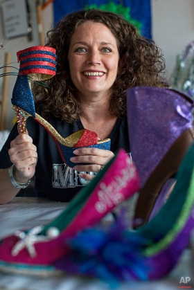Cari Rhoton, a lieutenant in an all-female Mardi Gras parade group known as the Krewe of Muses, creates the group's signature shoes from her garage in Kenner, La., Sunday, Jan. 10, 2016. Over 1000 members of the organization ride floats and pass out hand decorated shoes and other trinkets during Mardi Gras. (AP Photo/Max Becherer)