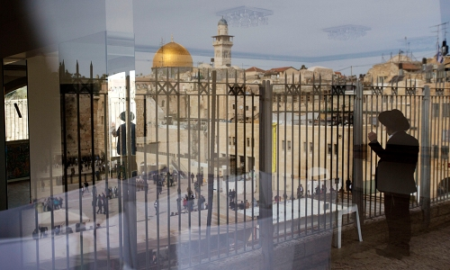 Seen through the reflection in a window, an ultra-Orthodox Jewish man looks at the Western Wall, the holiest site where Jews can pray in Jerusalem's Old City, Monday, Feb. 1, 2016. At center left is the Dome of the Rock. The Israeli government's decision to allow non-Orthodox Jewish prayer at Jerusalem's Western Wall is a major breakthrough for the country's long-marginalized liberal streams and their powerful supporters in the United States. (AP Photo/Sebastian Scheiner)