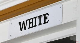 This Wednesday, Jan. 27, 2016 photo shows a sign marking the white entrance at the Montpelier Train Depot segregation exhibit in Orange, Va. Preservationists at President James Madison's Montpelier estate, where the white-and-yellow depot is located, decided to keep the segregated waiting rooms when the structure was renovated in 2010. (AP Photo/Steve Helber)