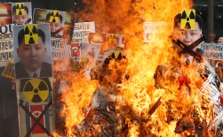 Pictures of North Korean flags, the North's leader Kim Jong Un and North's missiles are burned by anti-North Korea protesters during a rally in downtown Seoul, South Korea, Thursday, Feb. 11, 2016. Under the gaze of armed soldiers, large white trucks streamed across the world's most armed border Thursday as South Korean workers on Thursday began shutting down a jointly run industrial park in North Korea. The South's suspension will end, at least temporarily, the Koreas' last major cooperation project as punishment over Pyongyang's recent rocket launch.(AP Photo/Lee Jin-man)