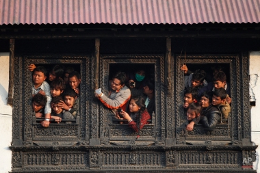 Nepalese people watch from the window of a Hindu temple the cremation of Nepalese prime minister Sushil Koirala, on the banks of the Bagmati River in Kathmandu, Nepal, Wednesday, Feb. 10, 2016. Koirala, who was a key figure in the drafting and adoption of the country's new constitution in 2015, died Tuesday at the age of 78. (AP Photo/Niranjan Shrestha)