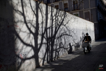 A man casts a shadow against a wall as he drives a motorbike in Madrid, Spain, Wednesday, Feb. 17, 2016. (AP Photo/Francisco Seco)
