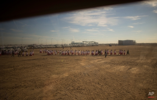 Photographed through a window, a children's choir walks to the entrance of the Abraham Gonzalez International Airport to greet Pope Francis before he arrives in Ciudad Juarez, Mexico, Wednesday, Feb. 17, 2016. The pontiff is scheduled to wrap up his trip to Mexico on Wednesday with a visit in a Ciudad Juarez prison, just days after a riot in another lockup killed 49 inmates, and a stop at the Texas border when immigration is a hot issue for the U.S. presidential campaign. (AP Photo/Ivan Pierre Aguirre)