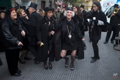 Members of the Alegre brotherhood dance outside a bar in Madrid, Spain, Wednesday, Feb. 10, 2016. The brotherhood stop in various bars for refreshments during a mock funeral procession which traditionally marks the end the carnival. (AP Photo/Paul White)