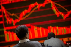 Chinese investors monitor stock prices in a brokerage house in Beijing, Thursday, Feb. 25, 2016. China faces pressure to reassure nerve-wracked world markets over how it is steering its slowing economy and managing its currency at Friday's gathering of finance ministers and central bankers from the United States, Europe and other major economies in Shanghai. (AP Photo/Mark Schiefelbein)