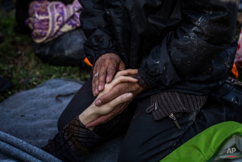 An Afghan man holds the hand of his wife after their arrival with other refugees and migrants from the Turkish coast to Mytilene, Lesbos island, Greece, Monday, Feb. 29, 2016. Border restrictions further north in the Balkans have left thousands of refugees and other migrants stranded in a country that is still wracked by its own financial crisis and unable to seal its lengthy sea border with Turkey. (AP Photo/Manu Brabo)