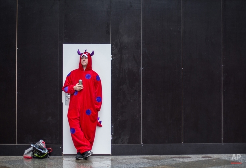 A carnival enthusiast leans against a wall and takes a break during the street Carnival celebrations in Cologne, Germany, Thursday Feb. 4, 2016. The street carnival has started in†Cologne under increased security measures. After a string of robberies and sexual assaults on New Year's Eve in the city that police say were committed largely by foreigners, German authorities are keen to avoid a repeat of those events during the five-day street party. (Maja Hitij/dpa via AP)