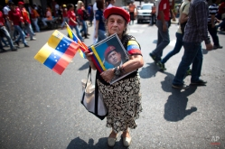 Marina Parra, 74, holds a picture of Venezuela's late President Hugo Chavez and wears his signature red beret during a parade marking the anniversary of his failed coup in Caracas, Venezuela, Thursday, Feb. 4, 2016. Chavez, a former paratrooper, led a failed coup in 1992 before being democratically elected president six years later. Chavez died of cancer in March 2013 at the age of 58. (AP Photo/Ariana Cubillos)