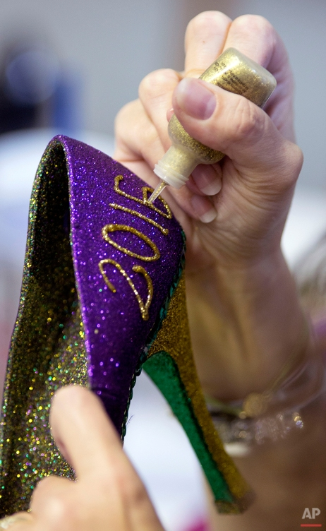 Cari Rhoton, a lieutenant in an all-female Mardi Gras parade group known as the Krewe of Muses, creates one of the group's signature shoes from her garage in Kenner, La., Sunday, Jan. 10, 2016. Over 1000 members of the organization ride floats and pass out hand decorated shoes and other trinkets during Mardi Gras. (AP Photo/Max Becherer)
