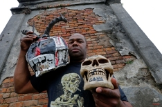 """Bruce """"Sunpie"""" Barnes, head of the Mardi Gras North Side Skull & Bone Gang, poses with his accoutrements for Mardi Gras day, in a cemetery in New Orleans, Thursday, Jan. 7, 2016. Their costumes are intended to represent the dead, and Barnes said they bring a serious message, reminding people of their mortality and the need to live a productive and good life. (AP Photo/Gerald Herbert)"""