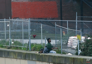 A man sits with his dog near downtown Seattle on Tuesday, Feb. 9, 2016. Seattle's struggle to respond to homelessness illustrates how challenging the issue is, particularly in one of the fastest-growing U.S. cities, in an area that is simultaneously dealing with skyrocketing rents, a heroin epidemic and declining federal housing support. (AP Photo/Ted S. Warren)