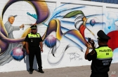 A police officer takes a photo of a colleague in front of a mural of Pope Francis, depicted as a graffiti artist, during a security drill for the route the pontiff will take while in Mexico City, Friday, Feb. 5, 2016. Pope Francis will arrive in Mexico on Feb. 12 and visit several cities. (AP Photo/Dario Lopez-Mills)