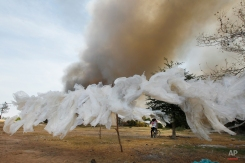 Cambodian boys sit on a bicycle near plastic bags as they watch smoke from a garbage dump at Kambol village on the outskirts of Phnom Penh, Cambodia, Friday, Feb. 5, 2016. (AP Photo/Heng Sinith)