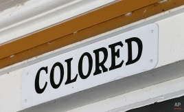 This Wednesday, Jan. 27, 2016 photo shows a sign marking the entrance to the colored area at the Montpelier Train Depot segregation exhibit in Orange, Va. Preservationists at President James Madison's Montpelier estate, where the white-and-yellow depot is located, decided to keep the segregated waiting rooms when the structure was renovated in 2010. (AP Photo/Steve Helber)