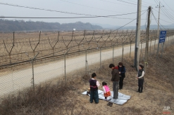 A South Korea family member pays to respect for their ancestors in North Korea, in front of the barbed wire fence as they celebrate the Lunar New Year at the Imjingak Pavilion, near the demilitarized zone of Panmunjom, in Paju, South Korea, Monday, Feb. 8, 2016. Millions of South Koreans visit their hometowns during the four-day holiday that began Sunday. (AP Photo/Ahn Young-joon)