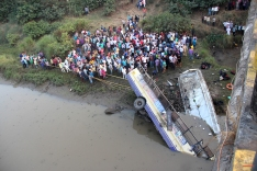 Locals gather in an attempt to rescue injured and recover bodies of passengers from the wreckage of the bus, in Navsari district of Indian state of Gujarat, Friday, Feb. 5, 2016. An official said the bus plunged off a bridge into the river below in western India, killing at least 25 people and injuring some 20 others. (AP Photo)