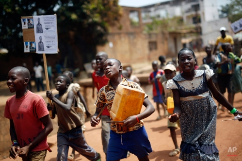 Children walk holding political placards in Bangui, Central African Republic, Wednesday Feb. 10, 2016. Two former prime ministers, Faustin Archange Touadera and Anicet Georges Dologuele, are running neck-and-neck in the second round of presidential elections Sunday Feb. 14 to end years of violence pitting Muslims against Christians in the Central African Republic. (AP Photo/Jerome Delay)
