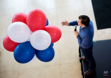 Balloons hang from the ceiling as Republican presidential candidate, Sen. Ted Cruz, R-Texas, right, speaks during a campaign event at a Toyota auto dealership Thursday, Feb. 4, 2016, in Portsmouth, N.H. (AP Photo/David Goldman)