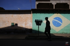 An army soldier walks in in front of a mural of the Brazilian flag during an operation to eradicate Aedes aegypti mosquito breeding sites, in the Brazlandia neighborhood of Brasilia, Brazil, Wednesday, Feb. 17, 2016. The Aedes aegypti mosquito is a vector for the spread of the Zika virus and it lives largely inside homes where it can lay eggs in even a bottle-cap's worth of stagnant water. (AP Photo/Eraldo Peres)