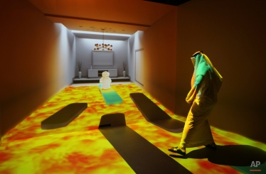 """An Emirati man plays at the """"Caring Machines"""" section of the Museum of the future during the opening day of the World Government Summit in Dubai, United Arab Emirates, Monday, Feb. 8, 2016. Those gathered for the World Government Summit in Dubai offered no immediate solutions to the crises gripping the region, like low global oil prices, global warming and the rise of violent extremism. But all acknowledged that keeping government responsive to its citizens remains crucial. (AP Photo/Kamran Jebreili)"""