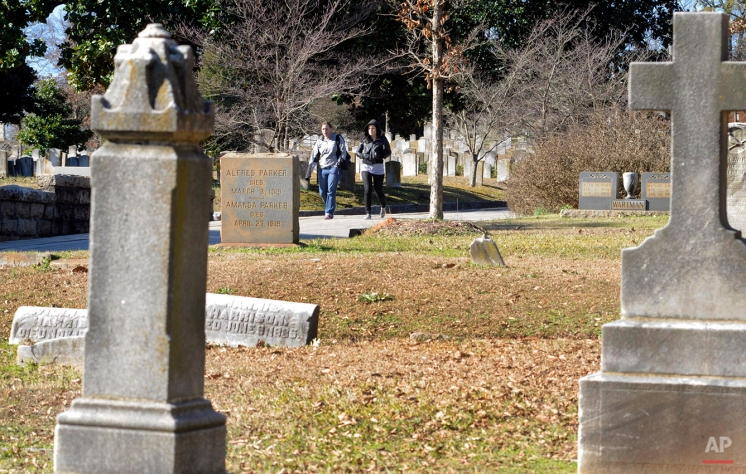 In this Monday, Jan. 18, 2016 photo, visitors walk through the black section of once-segregated Oakland Cemetery in Atlanta. (AP Photo/Jay Reeves)