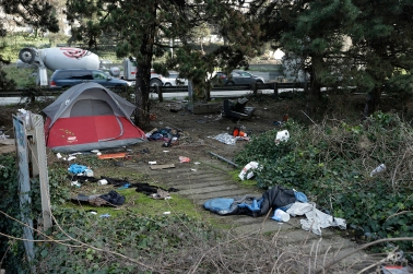 A tent and debris are shown next to the Interstate 5 freeway in downtown Seattle on Tuesday, Feb. 9, 2016. Some Seattle residents complain the city isn't acting fast enough to address the crime, drug use, garbage and other problems associated with unauthorized encampments. (AP Photo/Ted S. Warren)
