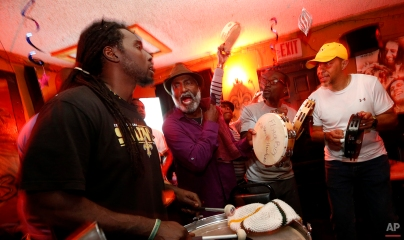 Members of the Mowhawk Hunters, a Mardi Gras Indian tribe, and the only tribe on the city's west bank of the Mississippi River, practice inside Sheila's Fantasy Lounge in New Orleans, Sunday, Jan. 3, 2016. (AP Photo/Gerald Herbert)