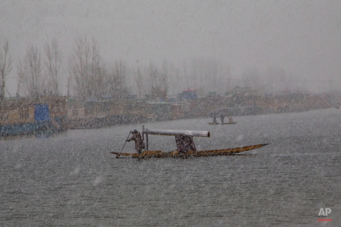 A Kashmiri man rows his shikara, a traditional wooden boat native to the region, in Srinagar, Indian controlled Kashmir, Thursday, Feb. 11, 2016. Following continued snowfall, the Jammu-Srinagar highway, that connects Kashmir valley to the rest of India, was closed to traffic, news reports said. (AP Photo/Dar Yasin)