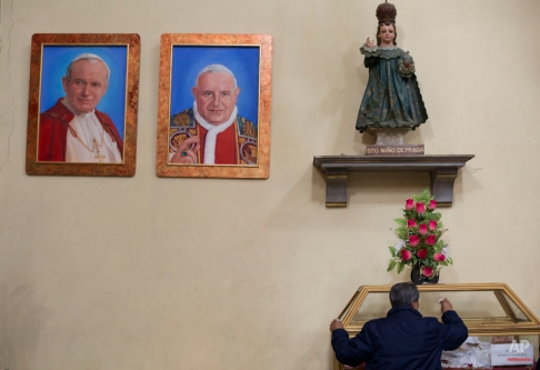 A worker cleans a glass case underneath portraits of Pope John Paul II, left, and Pope John XXIII, at the Metropolitan Cathedral in Mexico City, Wednesday, Feb. 10, 2016. Pope Francis will arrive to Mexico on Friday, Feb. 12 for a week-long visit. (AP Photo/Rebecca Blackwell)