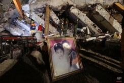 A recovered wedding portrait is propped up at the search and rescue staging area of a collapsed building complex in Tainan, Taiwan, Monday, Feb. 8, 2016. More than 100 people are believed to still be under the debris in a powerful quake that struck on Saturday, Feb. 6, during the most important family holiday in the Chinese calendar of the Lunar New Year. (AP Photo)