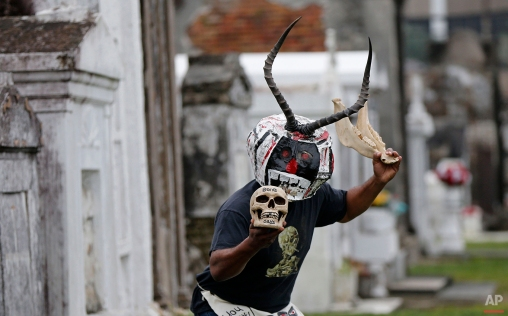 """Bruce """"Sunpie"""" Barnes, head of the Mardi Gras North Side Skull & Bone Gang, poses with his accoutrements for Mardi Gras day in a cemetery in New Orleans, Thursday, Jan. 7, 2016. Their costumes are intended to represent the dead, and Barnes said they bring a serious message, reminding people of their mortality and the need to live a productive and good life. (AP Photo/Gerald Herbert)"""