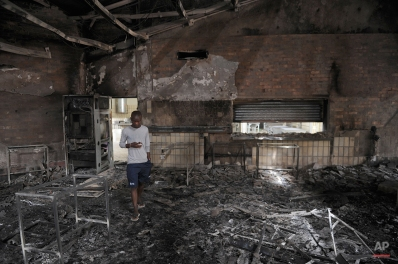 A student walks through the remains of the Science Center at the University of the North-West University in Mahikeng, South Africa, (also known as Mafikeng) Thursday, Feb. 25, 2016. Protesting students burned down several buildings on the campus Wednesday forcing the evacuation and indefinite closure until further notice spokesman said Thursday. (AP Photo)