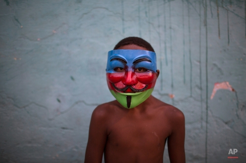 A youth wearing a carnival mask poses for a photo in a slum of Recife, Brazil, Friday, Feb. 5, 2016. Brazil has begun preparing for its pre-Lenten world famous festival that starts this weekend. (AP Photo/Felipe Dana)