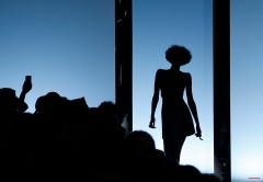 A model and spectators are silhouetted during Fausto Puglisi women's Fall-Winter 2016-2017 fashion show , part of the Milan Fashion Week, unveiled in Milan, Italy, Wednesday, Feb. 24, 2016. (AP Photo/Antonio Calanni)