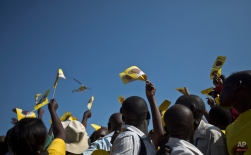Supporters of Uganda's long-time President Yoweri Museveni cheer as a helicopter they believe him to be in makes an overflight, before his arrival at a rally at the Kololo Airstrip in Kampala, Uganda Tuesday, Feb. 16, 2016. Opposition leader Kizza Besigye, in a close race with Museveni, said Tuesday he does not believe the election will be free and fair. (AP Photo/Ben Curtis)