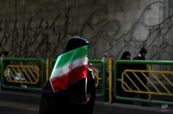 An Iranian woman holds the national flag during a rally commemorating the 37th anniversary of the Islamic revolution, in Tehran, Iran, Thursday, Feb. 11, 2016. The nationwide rallies commemorate Feb. 11, 1979, when followers of Ayatollah Khomeini ousted U.S.-backed Shah Mohammad Reza Pahlavi. (AP Photo/Ebrahim Noroozi)