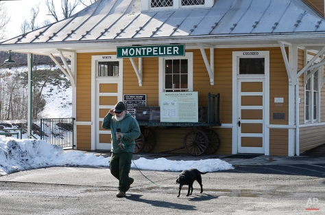 In this Wednesday, Jan. 27, 2016 photo, Montpelier IT manager, Richard Monroe, walks his dog past the Montpelier Train Depot segregation exhibit in Orange, Va. Preservationists at President James Madison's Montpelier estate, where the white-and-yellow depot is located, decided to keep the segregated waiting rooms when the structure was renovated in 2010. (AP Photo/Steve Helber)