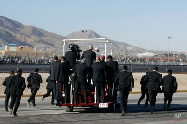 Security guards run alongside the popemobile transporting Pope Francis to a ramp near the Mexican-U.S. border fence, where he offered a prayer for migrants, in Ciudad Juarez, Mexico, Wednesday, Feb. 17, 2016. After a brief moment of prayer, Francis walked down the ramp and got back on his popemobile to head for the fairgrounds, where he celebrated his last Mass during a five-day Mexico tour. (AP Photo/Gregorio Borgia)