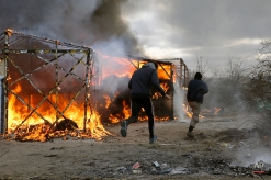 """Migrants run past burning tents in a makeshift camp near Calais, France, Monday Feb. 29, 2016. French authorities have begun dismantling part of the sprawling camp locally referred to as """"the jungle"""" where thousands are hanging out, hoping to make their way to a better life in Britain. (AP Photo/Jerome Delay)"""