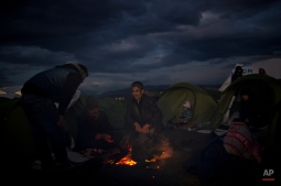 Refugees from Iraq warm themselves next to a makeshift fire, as they wait to be allowed to cross the the Greek-Macedonian border near the northern Greek village of Idomeni, Wednesday, Feb. 24, 2016. The Greek interior ministry said about 12,000 people have been stranded in Greece since neighbor Macedonia began turning Afghan immigrants away at the border and slowing the number of crossings for others heading to central and northern Europe. (AP Photo/Petros Giannakouris)