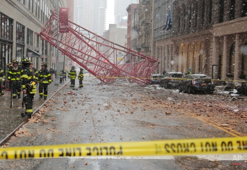 A collapsed crane lies along the street on Friday, Feb. 5, 2016, in New York. The crane landed across an intersection and stretched much of a block in the Tribeca neighborhood, about 10 blocks north of the World Trade Center. (AP Photo/Bebeto Matthews)