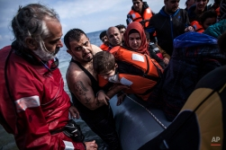 A Syrian man holds his son as they arrive with refugees and migrants on a dinghy from the Turkish coast to Mytilene, Lesbos island, Greece, on Thursday, Feb. 25, 2016. Balkan border controls leave thousands people stranded in Greece as the country scrambles to cope with border restrictions imposed recently by Austria and Balkan countries — while some 4,000 migrants and refugees continue to arrive on Greek territory daily. (AP Photo/Manu Brabo)