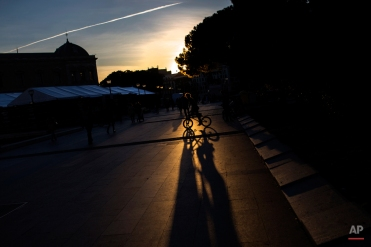 A youngster casts his shadow against the ground as he rides a bike at the Colon square in Madrid, Thursday, Feb. 4, 2016. The square, in honour of the explorer Christopher Columbus and located in a wealthy area of the Spanish capital, is frequented by commuters, tourists and skaters. (AP Photo/Francisco Seco)