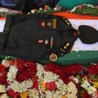 The uniform of India's National Security Guard commando Niranjan Kumar, who was among those killed in the attack on the Pathankot air force base, is placed on his coffin draped in an Indian flag, in Bangalore, India, Monday, Jan. 4, 2016. At least two gunmen were holed up in a two-story building on the Indian air force base near the Pakistan border and exchanging gunfire with troops Monday, more than two days after they and several others attacked the heavily fortified compound, officials said. (AP Photo/Aijaz Rahi)