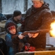 A military instructor helps a boy to shoot a rifle with blanks at a weapon exhibition during a military show in St. Petersburg, Russia, Sunday, Jan. 17, 2016. (AP Photo/Dmitry Lovetsky)