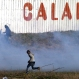 Migrants run away from tear gas thrown by police forces near the Channel Tunnel in Calais, northern France, Thursday, Jan. 21, 2016. Bulldozers moved in this week to clean the Calais migrant camp after hundreds of migrants began moving deeper into the squalid camp. Some fear the camp will eventually be razed to rid Calais of migrants. (AP Photo/Michel Spingler)
