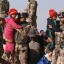 Jordanian soldiers carry Syrian refugee children stranded in the makeshift camp into Jordanian territory through the Hadalat border crossing, located near the northeastern Jordanian border with Syria and Iraq, near the town of Rewashed, Jordan, Thursday, Jan. 14, 2016. (AP Photo/Raad Adayleh)