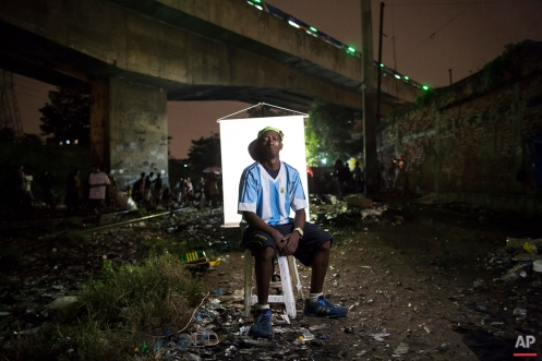 """In this March 17, 2015 photo, Sancler Rodrigues, 32, poses for a portrait in an open-air crack cocaine market, known as a """"cracolandia"""" or crackland, where users can buy crack, and smoke it in plain sight, day or night, in Rio de Janeiro, Brazil. Rodrigues said he has been smoking crack for 7 or 8 years. """"I didn't think my old black shirt would look good in your photo, so I borrowed this from friend,"""" Rodrigues said. (AP Photo/Felipe Dana)"""